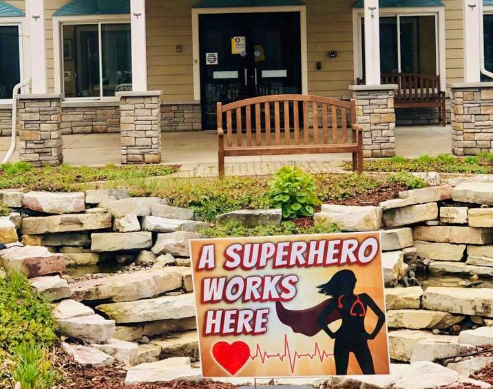 Assisted Living and Covid-19. Yard sign in front of building that says A super hero works here